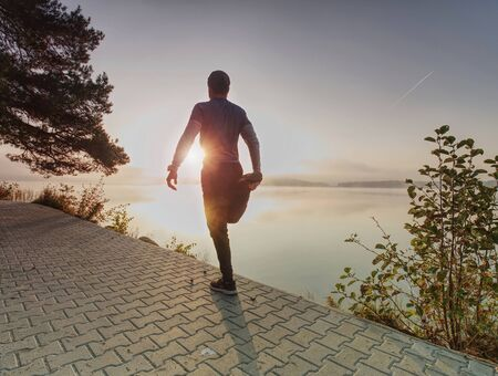 Runner stretching Leg in front of river. Athletic sport man stretching leg muscles before run and jog in nature training workout Imagens