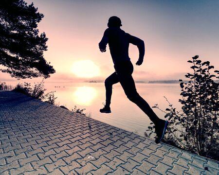 Regular run at lake. Man runner sprinting outdoor in scenic nature. Fit muscular male athlete training trail running for marathon run.