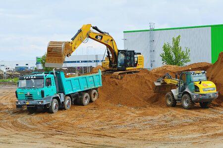 Koparki kopią i ładują wykop na ciężarówkę na placu budowy. Hydrauliczna ciężarówka typu showel fill. . 10 maja 2019, Plasy Czechy.