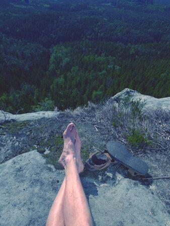 Les jambes poilues mâles avec des sandales reposent sur un sommet rocheux au-dessus de la vallée du parc naturel. Journée d'été ensoleillée paresseuse.