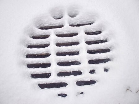 Manhole covers after snowfall covered by snow. Snow Covered Sewer enter. Pattern of snow deposits on a metal grid