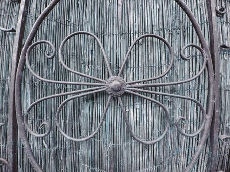 Simple ornaments in fence, wrought-iron gate. Traditional ornamental forging