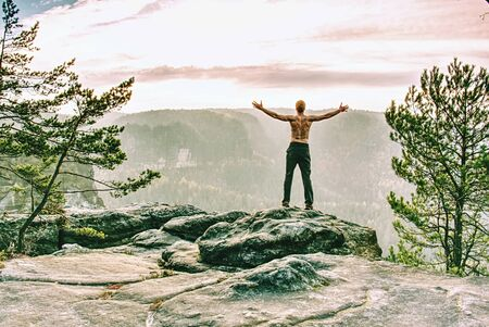 Muscular sports man shirtless standing on rock against the misty mountains. Rests on top of mountain peak