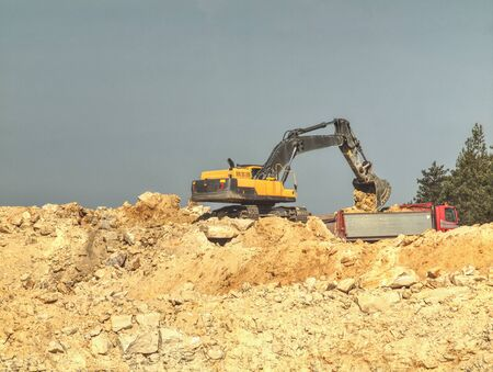 Excavator digger stone and Dump truck working on construction site,  loader on the hill Stockfoto