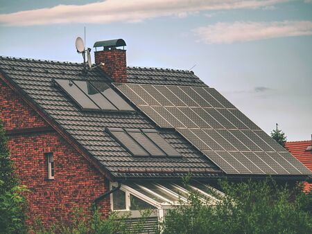 Family house with solar panels on roof against blue sky with clouds