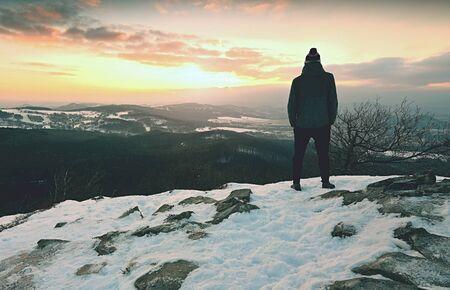 Man on rocks and looking at snow-covered hills. Dark sky with clouds. Zdjęcie Seryjne - 131716999
