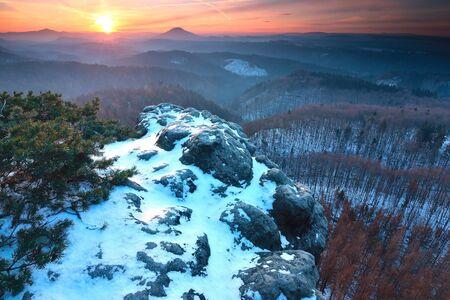 Blue spring daybreak, thawing of last snow. Sandstone cliff above deep misty valley. Standard-Bild - 131717049