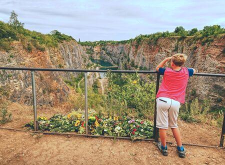 Junge bleibt in der Nähe des Todesortes. An diesem Ort ist die Erinnerung an die Opfer gestorben. Blumen am Handlauf über altem geschlossenem Bergwerk. Der Gedenkort. Standard-Bild