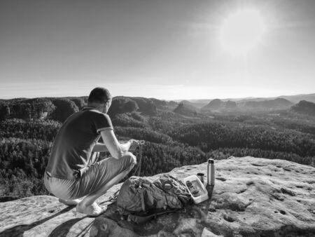 Climber man sit on rock, prepare for eating snack during rest from extreme rock climbing