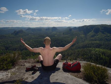 Bare-chested man sit on peak over mountains. Handsome shirtless man during outdoor Yoga exercise Stockfoto