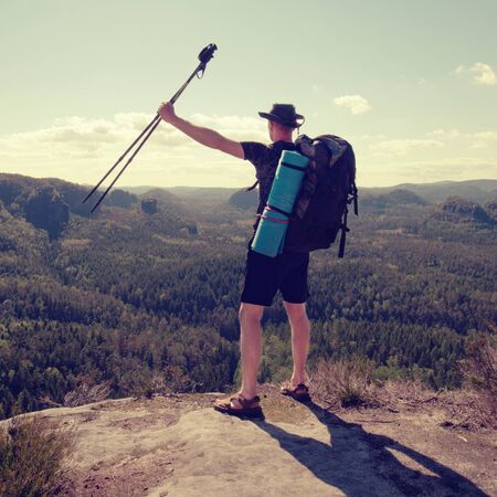 Traveler with backpack and trekking sticks looks on a mountain peak. Hiker with sleeping pad. Stock Photo