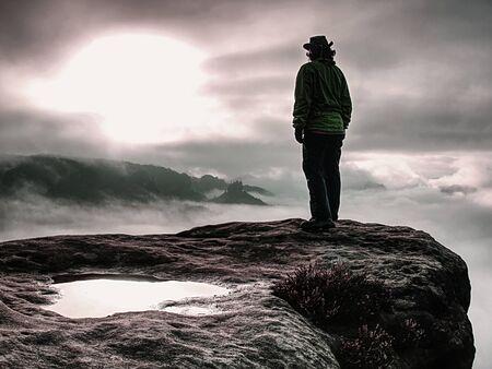 Cow girl in cowboy hat on mountain summit looking into heavy mist in dark landscape. Sun is lightning few places in dark clouds.