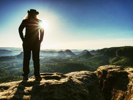 Successful woman hiker cheking the altitude on top of sandstone sharp cliff edge.