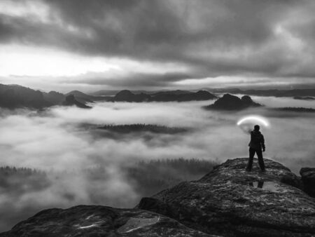 Woman bring the light on mountain to give light to whole world in darkess. Silhouette of woman standing against misty night landscape Stock fotó