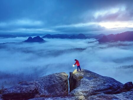 Beautiful lost woman hold in hands bright shining lamp on mountain summit. Alone woman tourist lighting into landscape around. Stock Photo