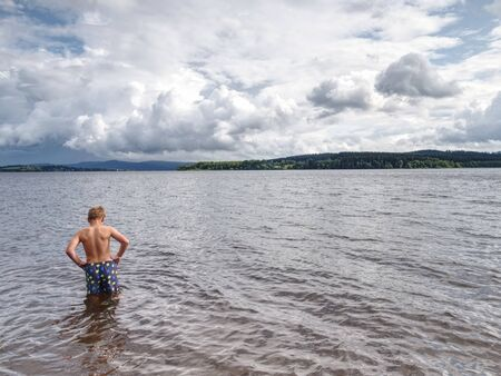 Little joyful Caucasian funny boy try cold water of lake.  Kid stay in water with level at knee