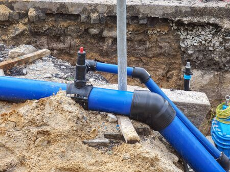 HDPE plastic tubes for drink water. Reneval potable water system in the city. Laying drink water pipe at the corner of a flat house Stok Fotoğraf