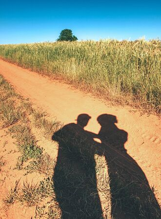 Shadows play man and woman stand hold hands. Shadows on dirty dusty road between field.