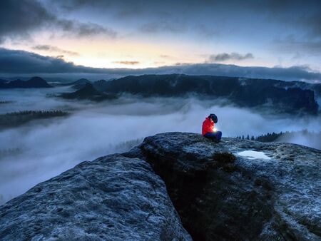 Nice woman sit on summit in hands holding flash bolb. Girl waiting in darkness for sun in high mountains during blue hour.