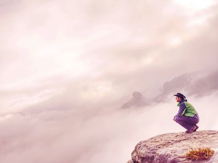 Man sitting on cliff enjoying mountains and clouds landscape. Travel happy emotions Lifestyle concept. Young peaople traveling active adventure vacations