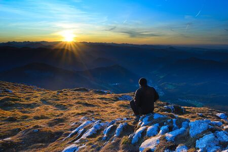 Man in black outdoor clothes sit on cracked rocky summit in Alps watchin amazing sunset Stok Fotoğraf - 132615044