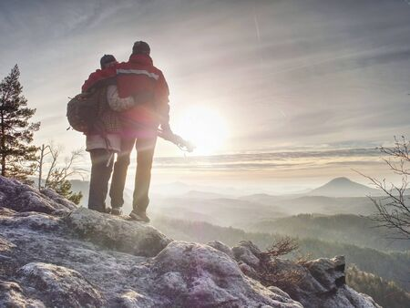 Couple of hikers look down into fogy valley. Photographer stay on cliff and takes photos. Dreamy fogy landscape blue misty sunrise in a beautiful valley below Stok Fotoğraf