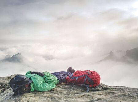 Woman tourist lays on top of the word above heavy clouds and dreams. Hiker wear green jacket and leather cow boy hat. Red backpack at girl hip.