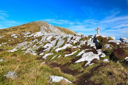 Stony pyramid with wooden mascot shows direction on Alpine gravel mountain summit. Daybreak horizon above blue foggy valley Stok Fotoğraf - 132614321