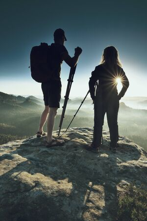 Two photographers meet at sunrise or dawn in the mountains. Blond hair girl with tall slim guy talk about photography.