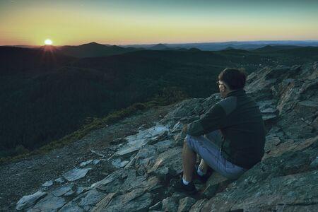 Man enjoying morning and looking to orange daybreak at misty horizon. Adult tourist in black sit on cliff's edge Stok Fotoğraf - 132614546
