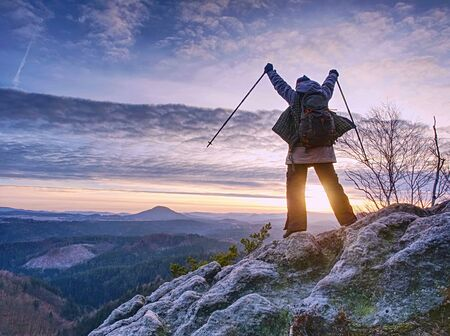 Women adventure, travel and hike people concept. Happy smiling woman walking with backpacks over sharp rocks in autumn morning. Stok Fotoğraf - 132614794