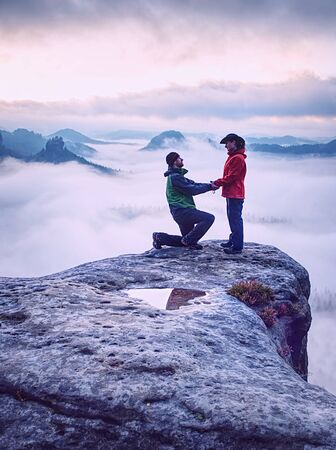 Silhouettes of hugging man and woman on mountain peak at misty sunset. Foggy landscape with silhouette of couple people against cloudy sky