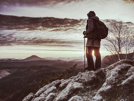 Woman reached mount peak. Girl wearing backpack and sunglasses, using trekking sticks, enjoying cloudy daybreak. Outdoor activity, tourism concept