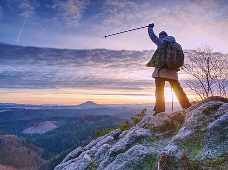 Women adventure, travel and hike people concept. Happy smiling woman walking with backpacks over sharp rocks in autumn morning.