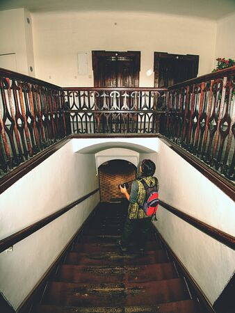 Black hair woman photographer study interier of old house with renewal wooden stairs and wooden handrails around staircase. Foto de archivo