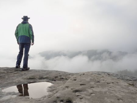 Man ranger stay alone on the edge mountain ridge above heavy clouds. Travel adventure lifestyle extreme vacations