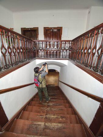 Une photographe aux cheveux noirs étudie l'intérieur de la vieille maison avec des escaliers en bois de rénovation et des mains courantes en bois autour de l'escalier.