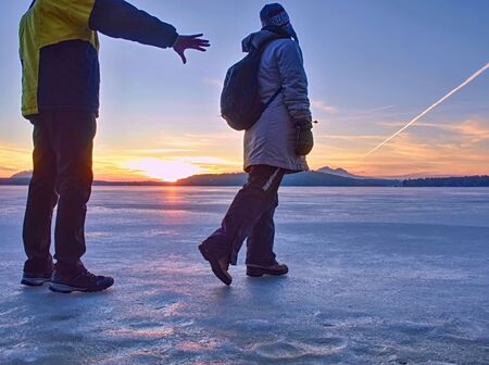 Tourist couple is spending time outdoors on a frozen lake, watching rising sun at horizon. Foto de archivo - 133516591