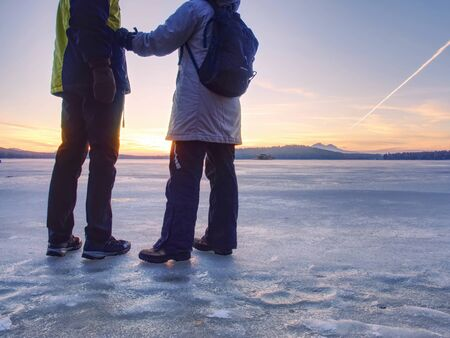 Couple, man and woman walking on the ice on a frozen lake. Happy couple on a frozen lake on a winter day