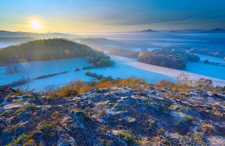 Exposed rocky mountain and sunset in the background, hoarfrost on meadows bellow Reklamní fotografie