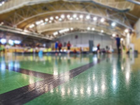 Black corner lines on green floor of inside court. Blurred people playing floorball in green court. Archivio Fotografico - 133516714