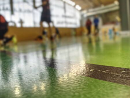 Green floor in school gym in details. Court of Sports Club with marked lines..
