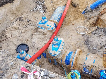Blue water pipes and shut-off valve on 300mm pipe with  plastic tube branch. Repairing of drink water system. Open excavation pit. Foto de archivo