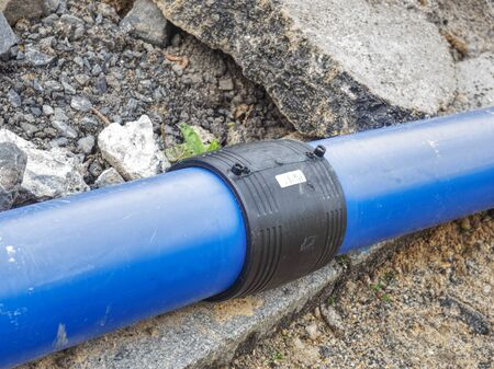 Welded black joint between two blue HDPE tubes for drink water delivery. Repairing of water supply system.