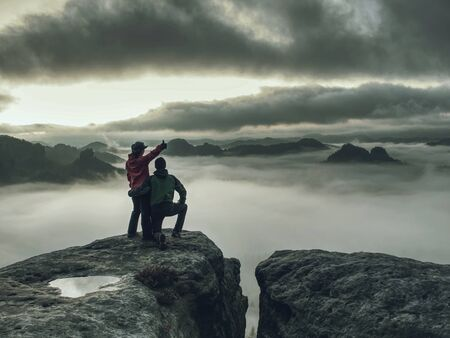 Hikers woman and man in dark sportswear on highest mountain and watch sunrise in darkness.  Trail on rocky edge above misty valley. Tourist couple enjoy life together