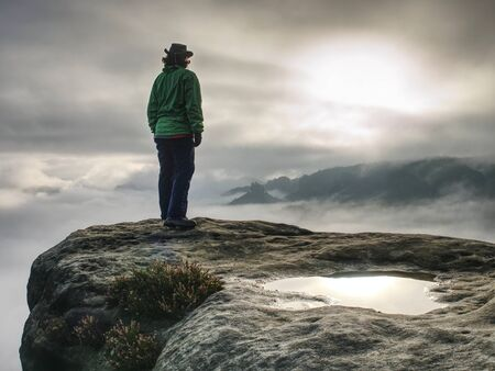 Silhouette of a cow girl or cowboy stay on rocky edge and watching down in the mist behind her or him