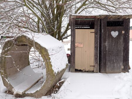 Dry wc. Wooden and secret place, heart on the door and snow around. Reklamní fotografie