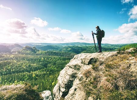 Man creator and photographer is setting up tripod for standing on rocky cliff.