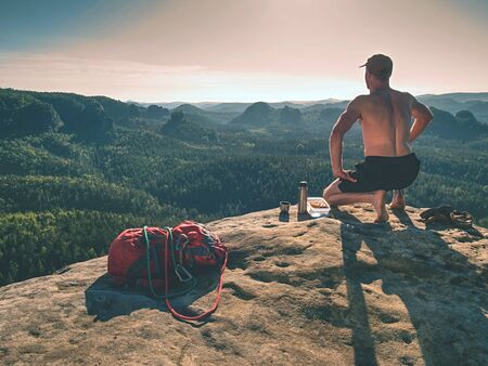 Naked sportsman having picnic. Toples climber sit and eat sandwich and drink from stainless flask bottle tea or coffee.