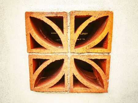 Ventilation hole fulfiled by the decorative perforated bricks block. House wall with perforated red brick